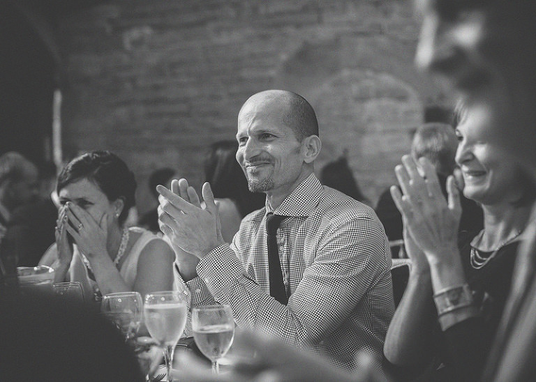 A man claps his hands after listening to the grooms speech