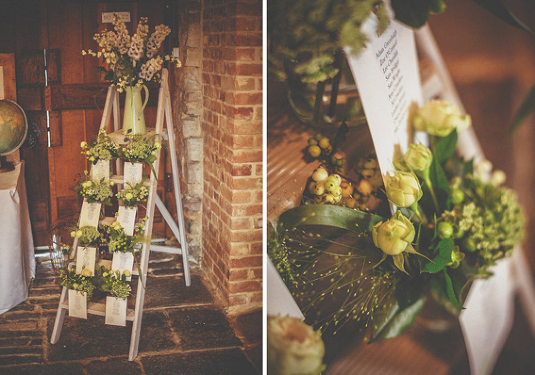 A wodden ladder in the corner of the barn with flowers on the steps