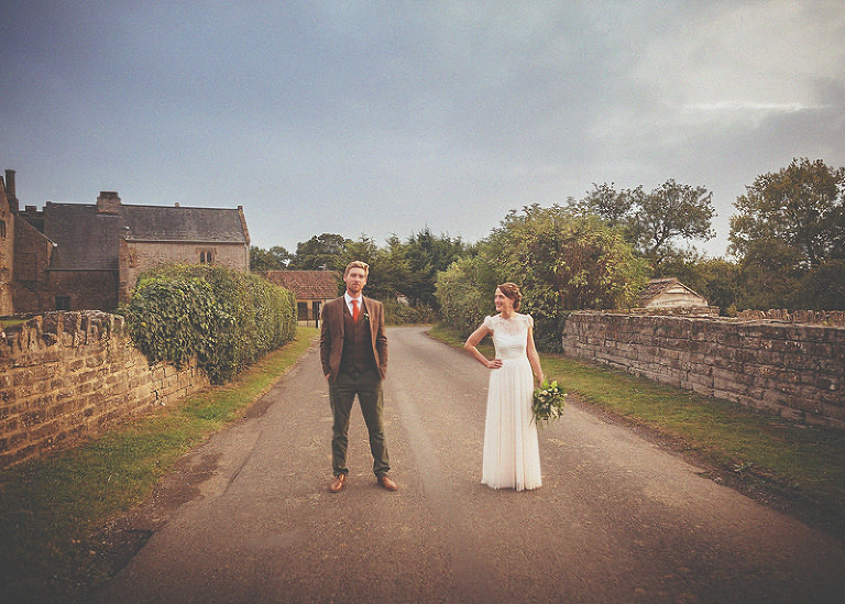 The bride and groom stand in the middle of the road outside Almonry Barn