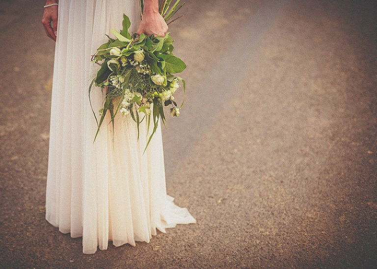 The bride stands in the middle of the road holding her bouquet next to her side