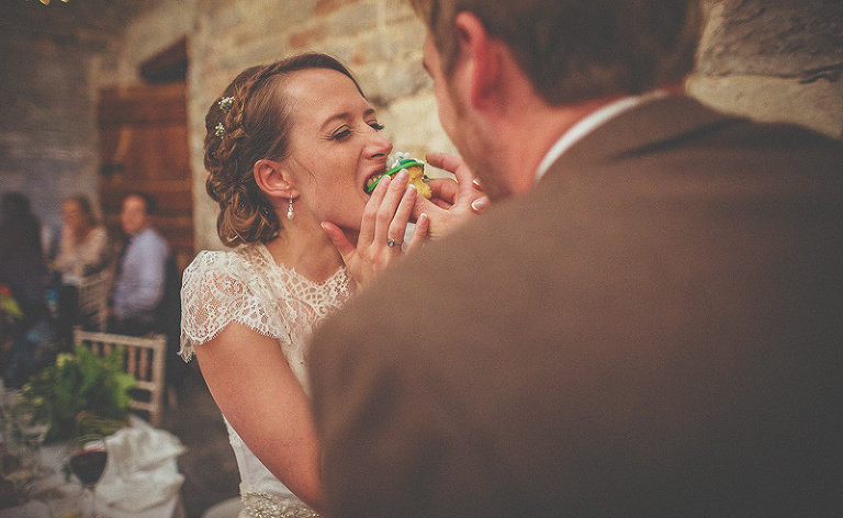 The groom puts a cupcake in the mouth of the bride