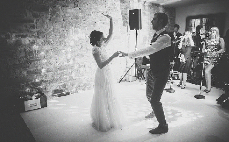The bride raises her left arm in the air and laughs with the groom on the dancefloor