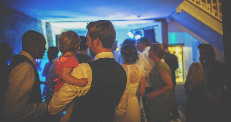 The groom holds a little girl in his arms on the edge of the dancefloor