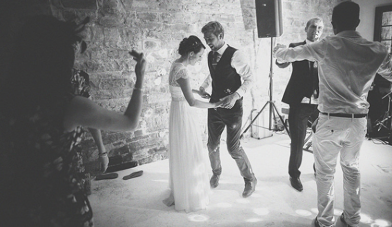 The bride and groom dancing with friends and family on the dancefloor at Almonry Barn