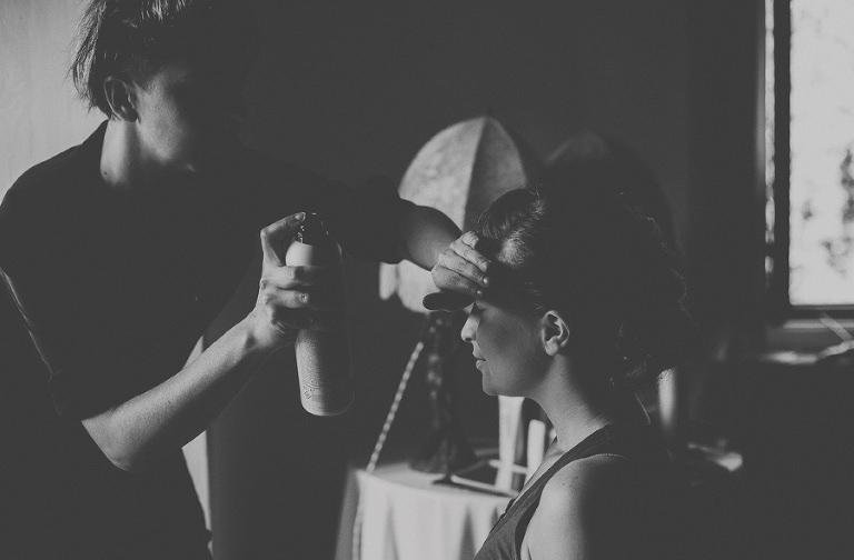 The italian hair stylist sprays hair spray on a bridesmaids head