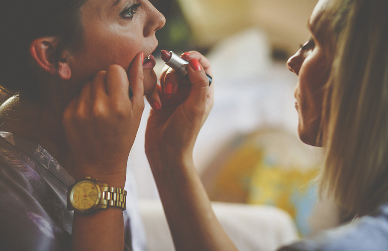 Lipstick is applied onto the brides lips