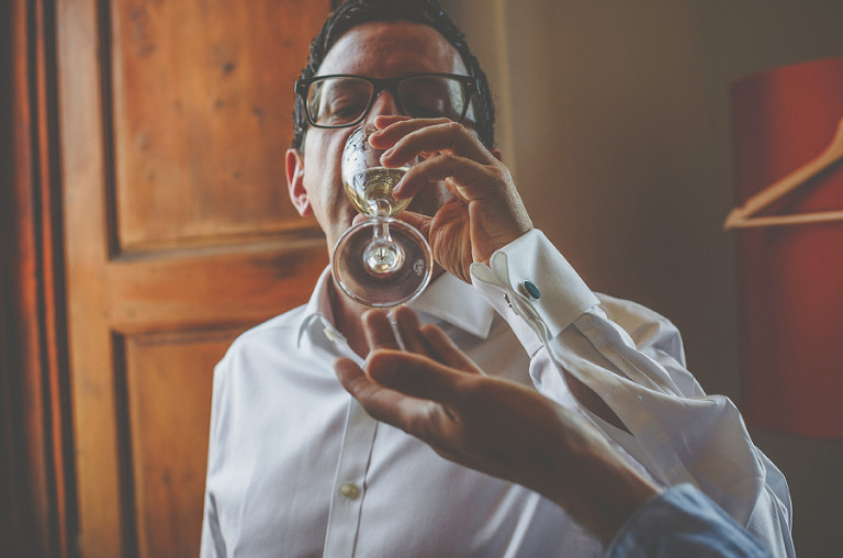 The groom drinks a glass of champagne