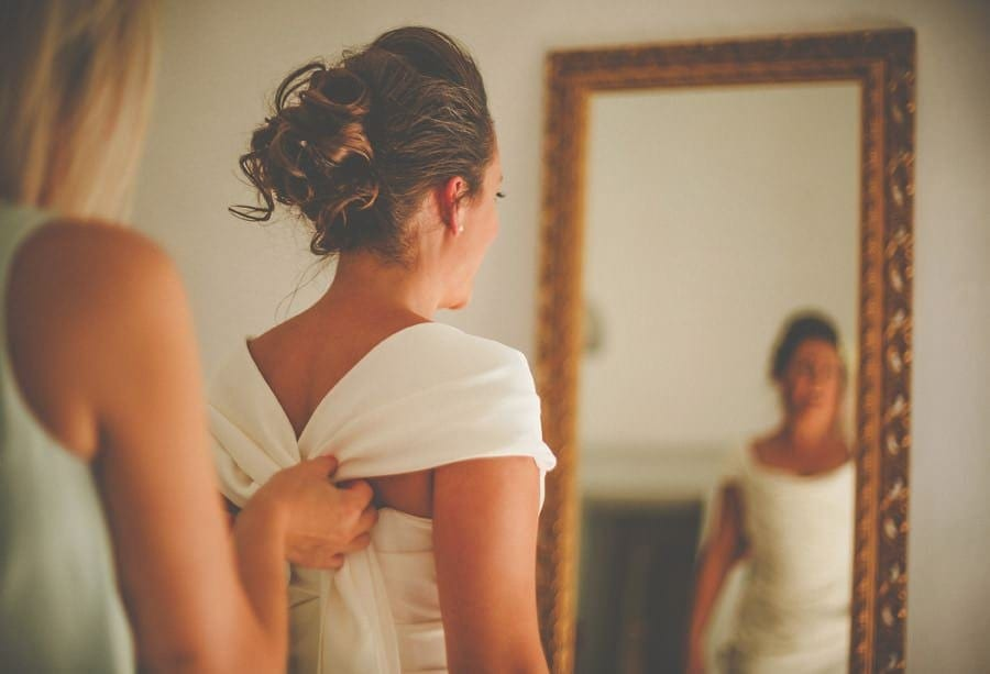 One of the bridesmaids straightens the wedding dress