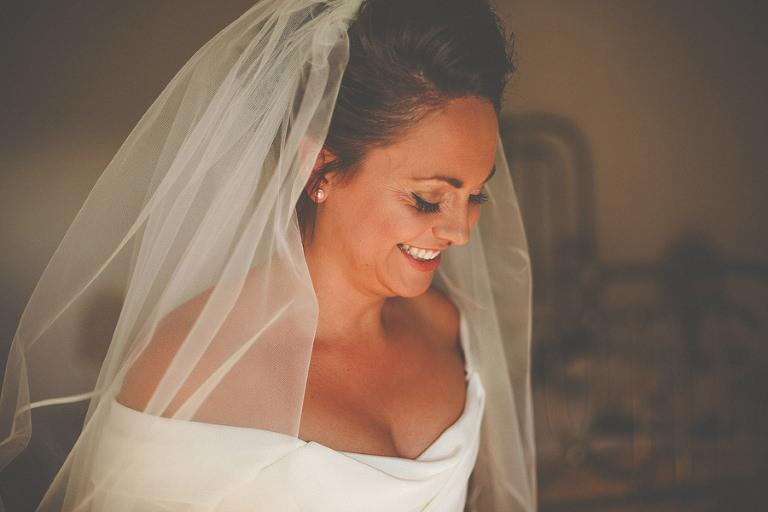 The bride looks down and smiles at villa di ulignano
