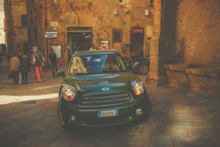 The wedding car drives through the old town of Volterra