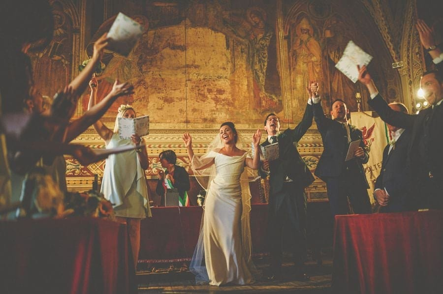 The wedding party stand up and sing together with arms raised high