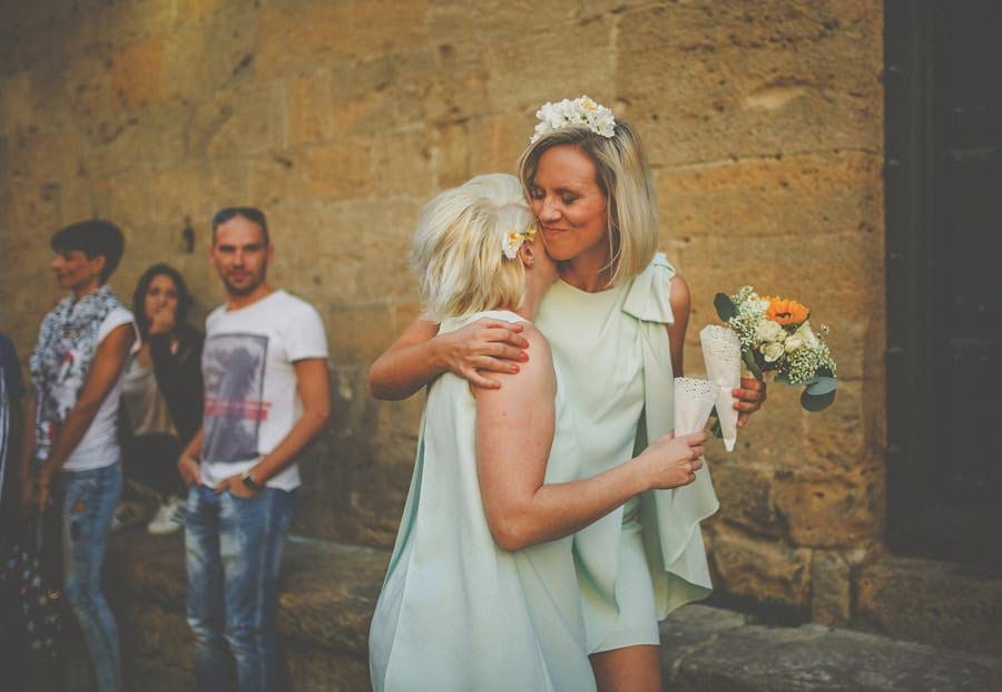 A bridesmaid hugs her friend outside the old town hall