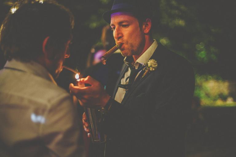 A man lights a cigar for his friend on the dancefloor