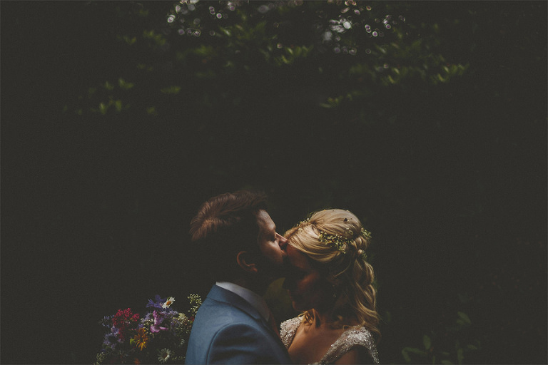 The groom kisses his bride on the forehead