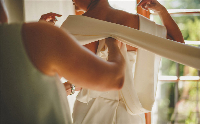 A bridesmaid fastens the back of the brides dress in the bridal suite
