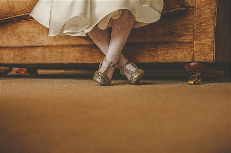 A flowergirl sits on the sofa and waits for the bride and bridesmaids