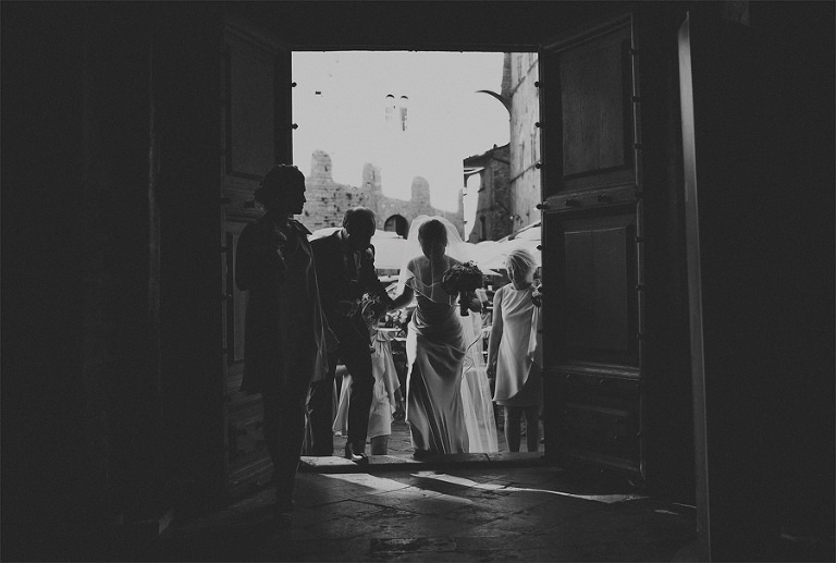 A bride enters the doorway of a church