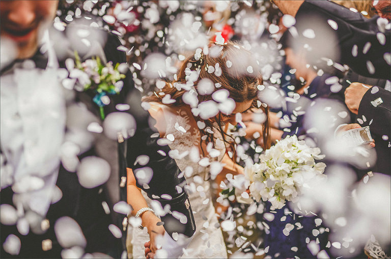 A bride and groom leave the church and are showered in confetti