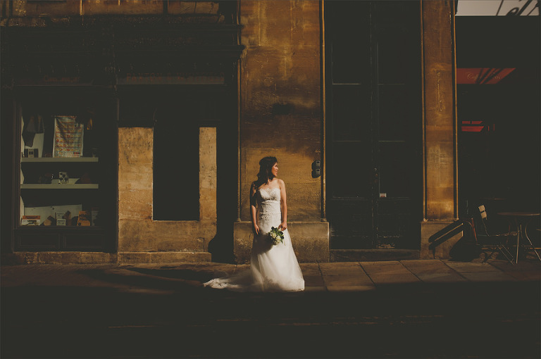 A bride stands on the street with her bouquet