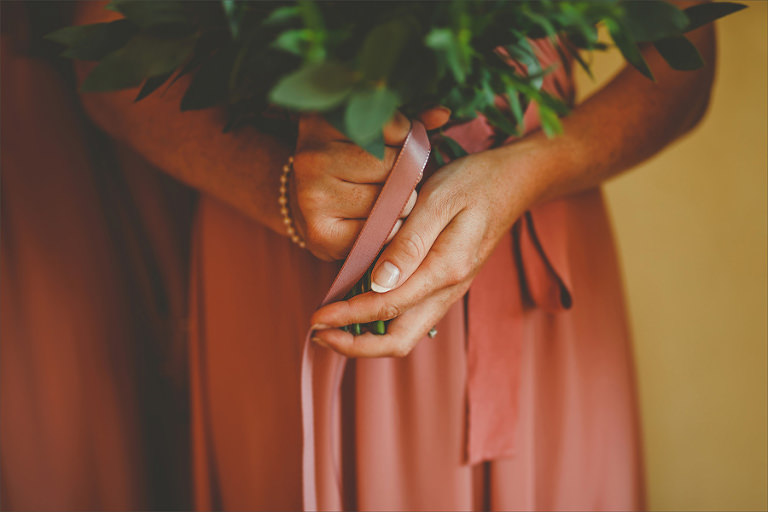A bridesmaid holds her flowers