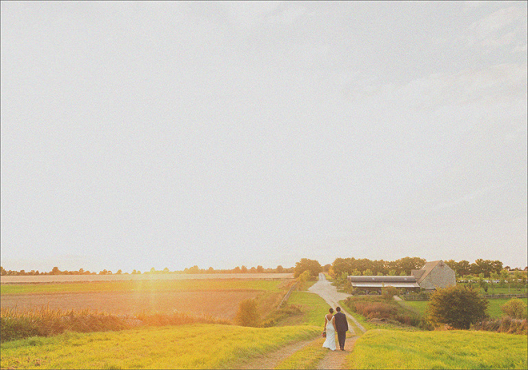 A bride and groom walk hand in hand together through the countryside