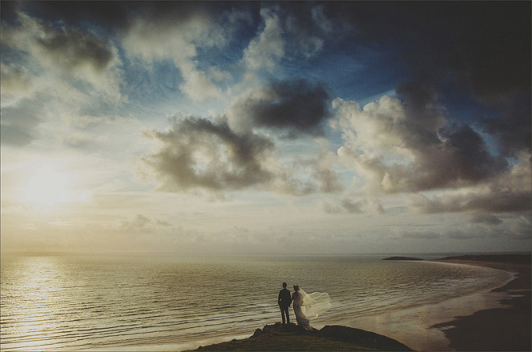 A bride and groom hold hands together and watch the sunset over the sea
