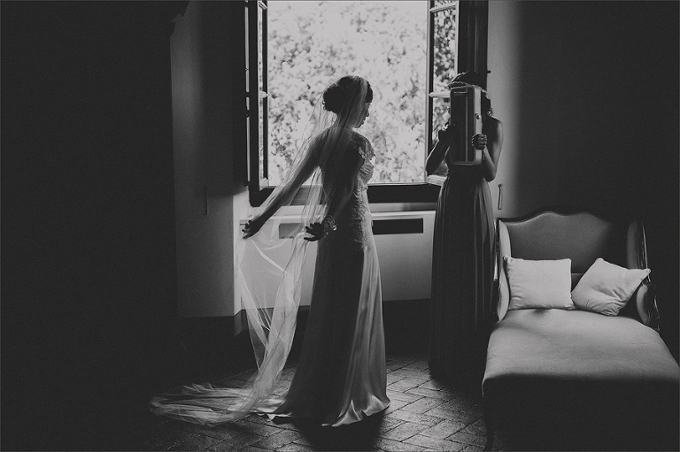The bridesmaid holds a mirror next to the window and the bride straightens her veil