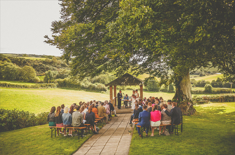 The wedding party sit next to each other and listen to the outdoor wedding ceremony