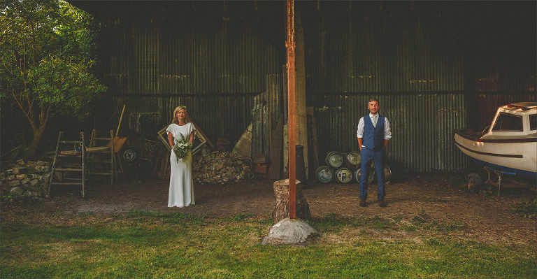 The bride holds her bouquet and stands next to the groom in a barn