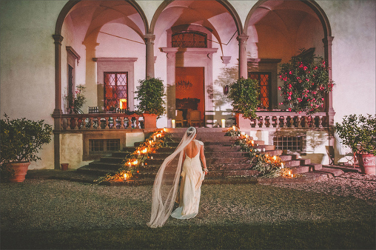 A bride stands in the courtyard of a large mansion