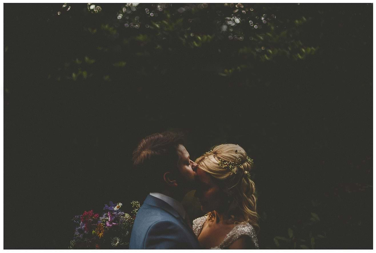 The groom kisses his bride on the forehead in the forest