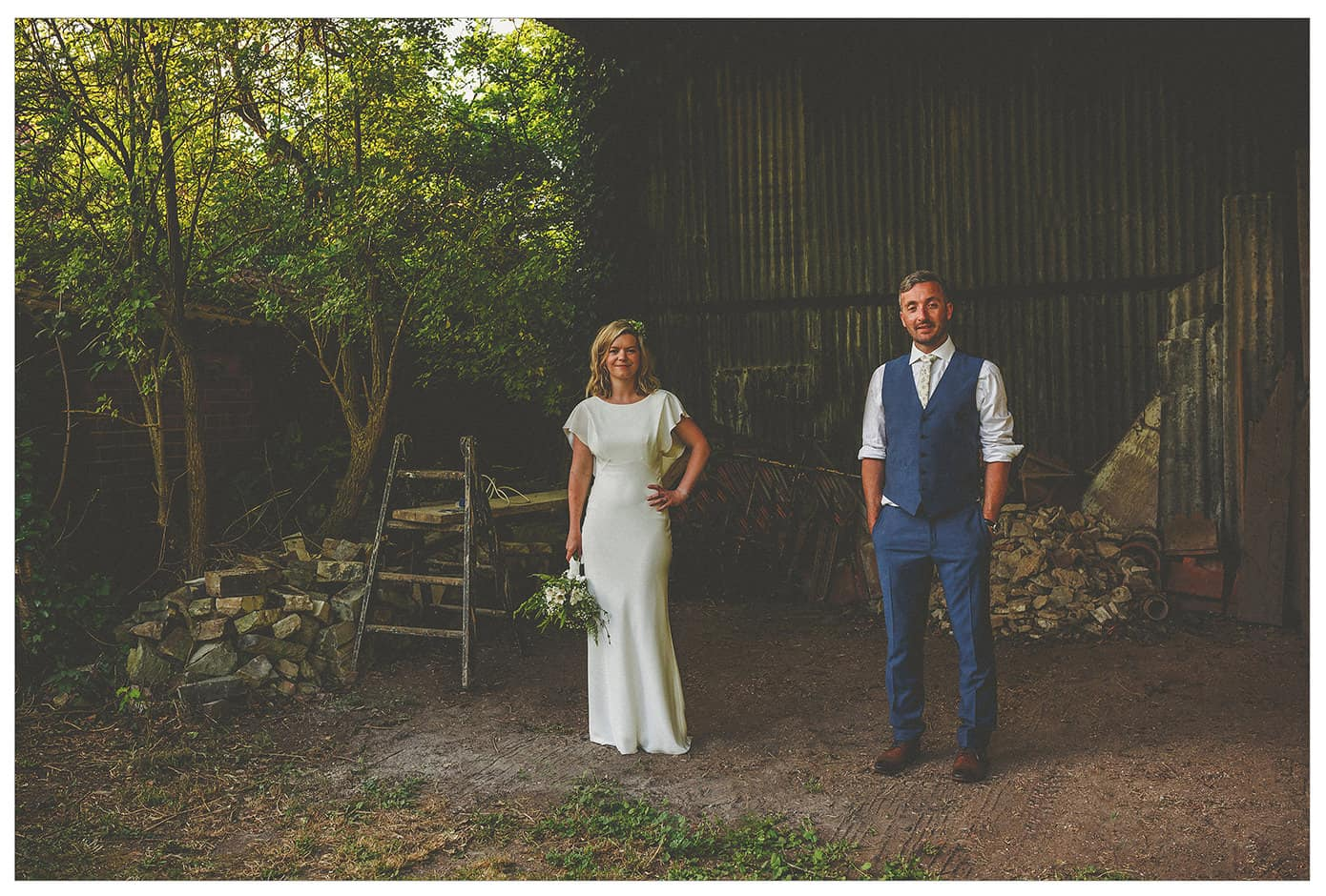 A bride and groom stand next to each other in a barn