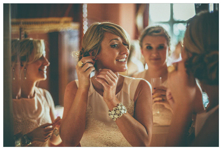 The bride looks into a large mirror and smiles in her hotel room