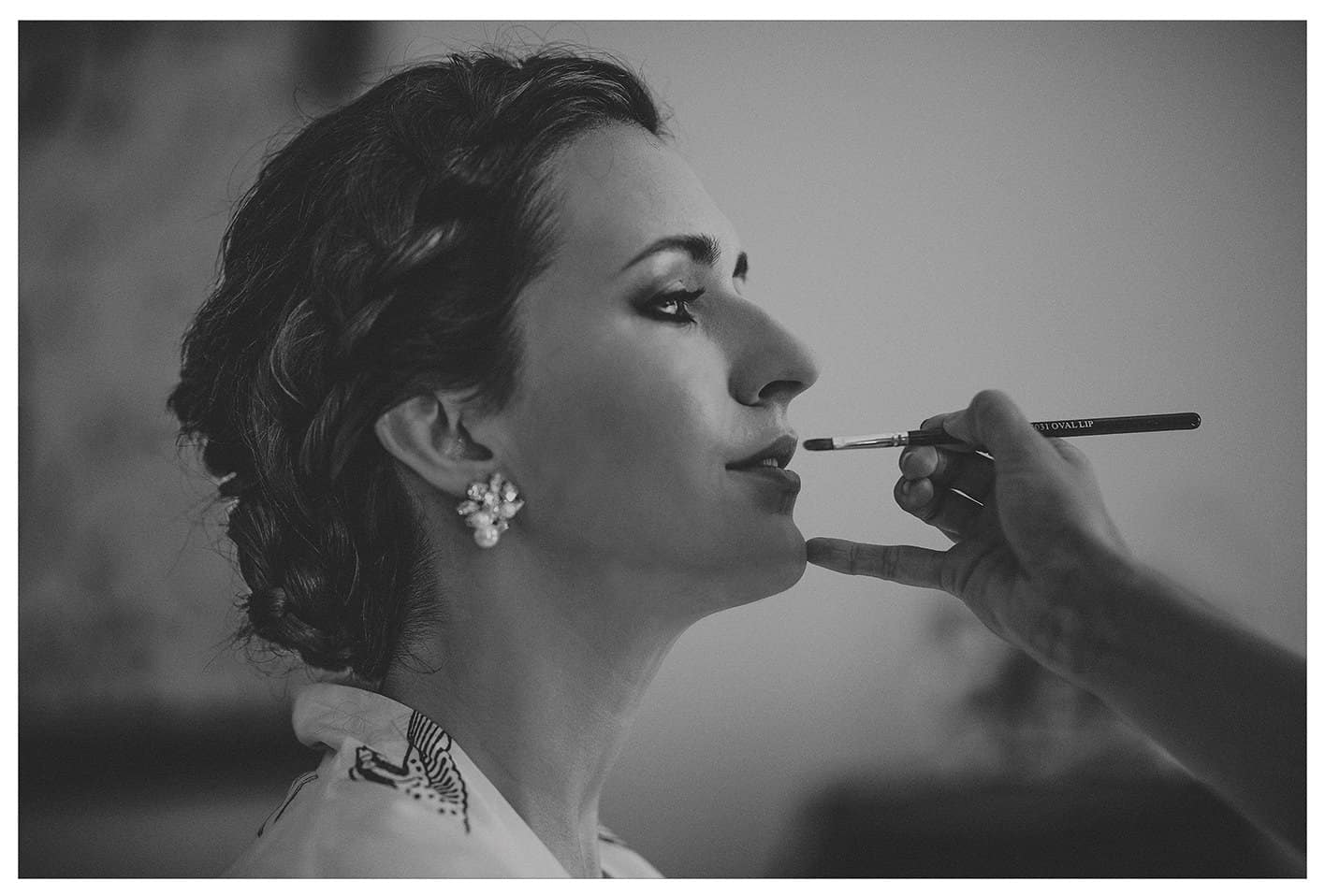 The make up artist applies lipstick onto the lips of the bride