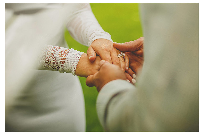 A bride and groom hold hands at an outdoor wedding ceremony in Frome