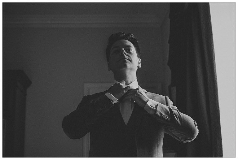 A groom looks in the mirror and straightens his tie in his hotel room