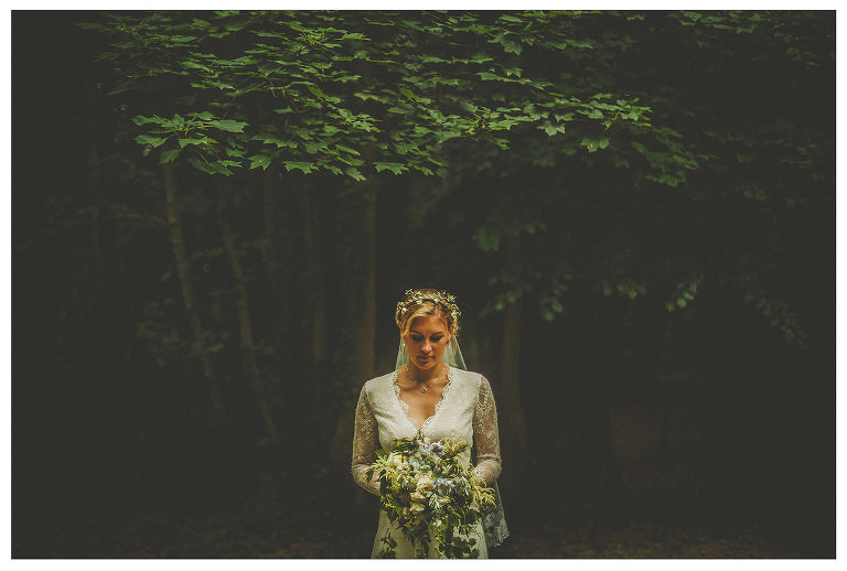 A bride looks at her flowers as she stands under a tree in the Frome countryside