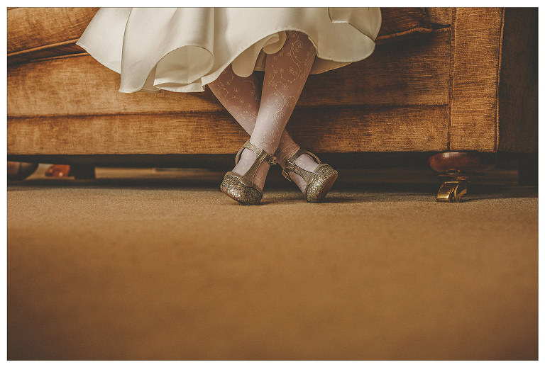A flowergirl crosses her legs and sits on a large settee