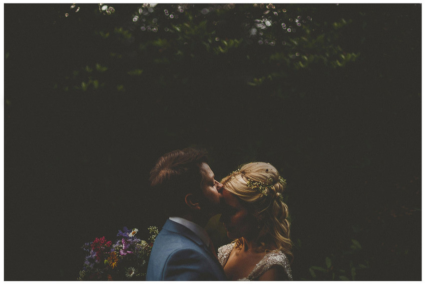 A gtoom kisses his bride on the forehead in a forest