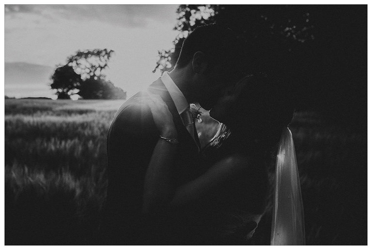 The bride and groom kiss each other as the sun goes down over the Mendips countryside