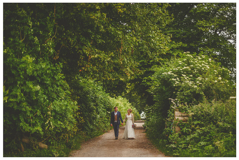A bride and groom walk through the countryside