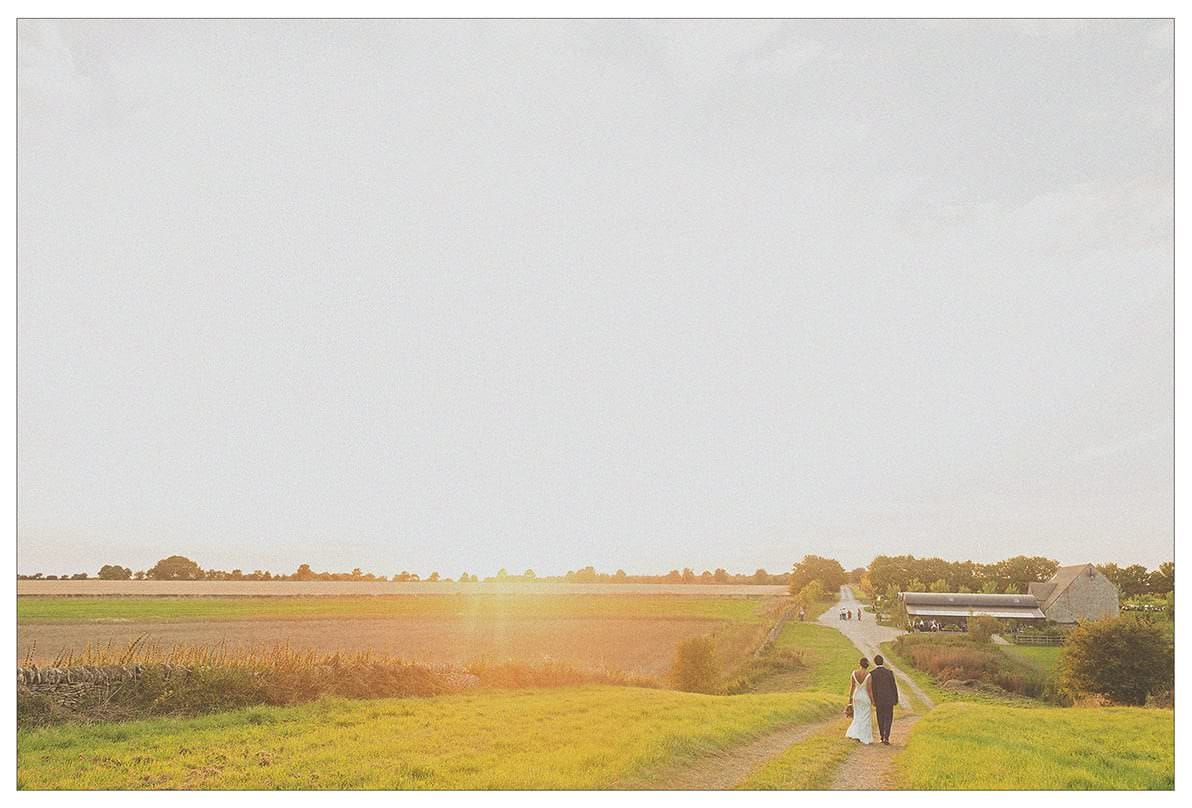 A bride and groom watch the sun go down as they walk through the countryside