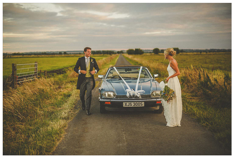 A bride and groom walk away from their car in the countryside