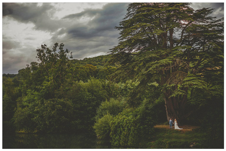 The bride and groom stand next to each other under a tree next to a lake in the countryside