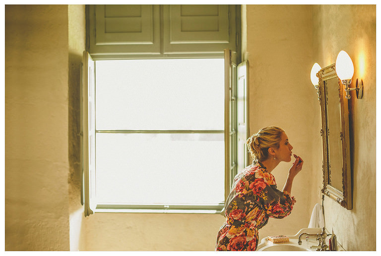 A bride puts on her lipstick in front of a large mirror next to the window