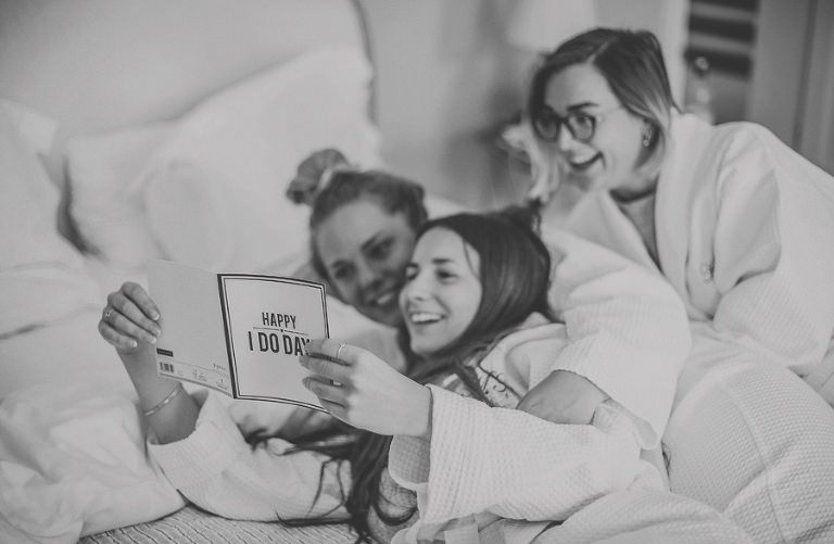 Bridesmaids reading wedding cards on the bed