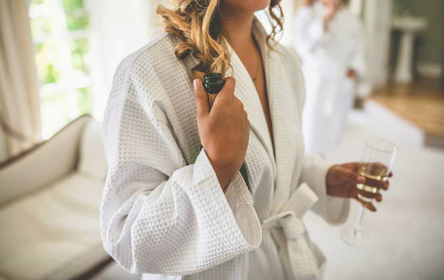 The bride holds a bottle of champagne in her hand