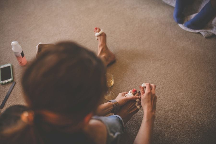 A wedding guest paints her toe nails