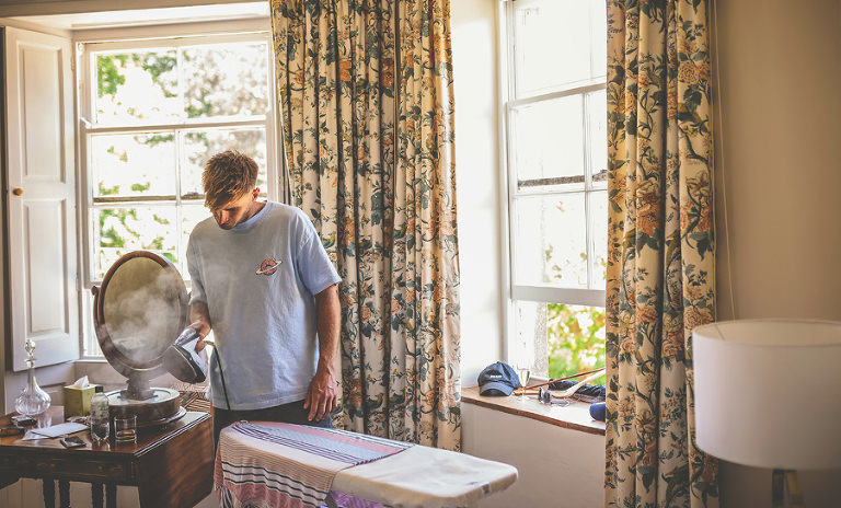 A wedding guest irons his shirt at Pennard house, Somerset