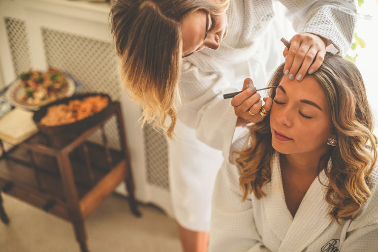 The bride has her makeup applied by a friend